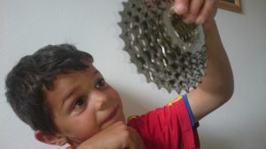 Small boy looking at gears