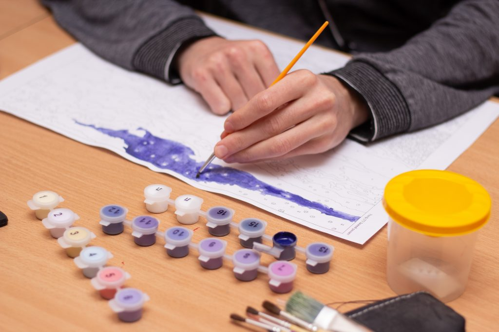 Man painting a colour by numbers drawing, which can explain some of the ideas in computing and STEM